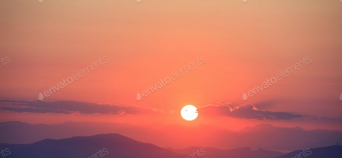 Beautiful sunset on sky over mountains background. The sun is in the middle.