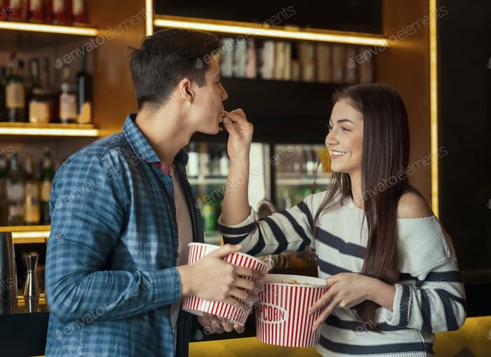 Young couple eating popcorn in cinema cafe