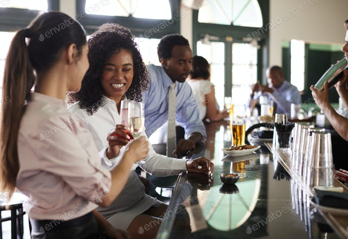 Two Businesswomen Meeting For After Works Drinks In Bar