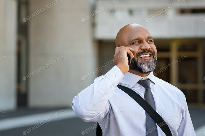African mature businessman talking on phone outdoor