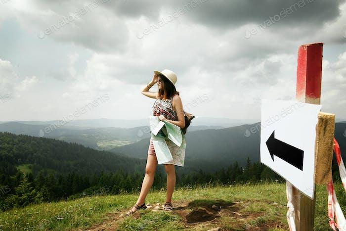 Frau Reisende mit Rucksack hält Karte und Erkundung auf den Bergen