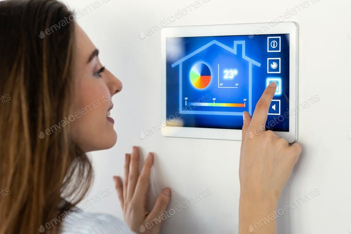 Pretty young woman using the home automation system on digital tablet to regulate the temperature.