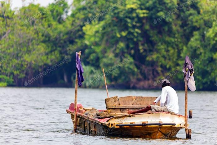 Traditional Sri Lankan fisherman in river back view