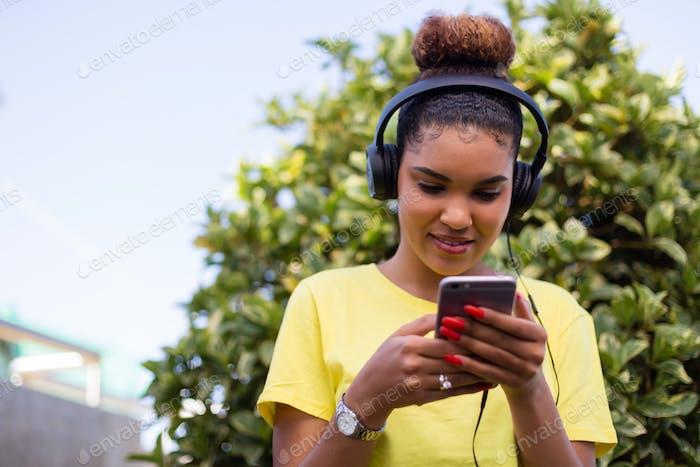 Ziemlich junge schwarz afrikanische amerikanische Frau hören Musik mit einem Kopfhörer im freien