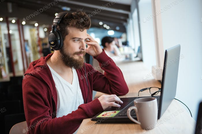 Boy with beard using laptop and listening to music