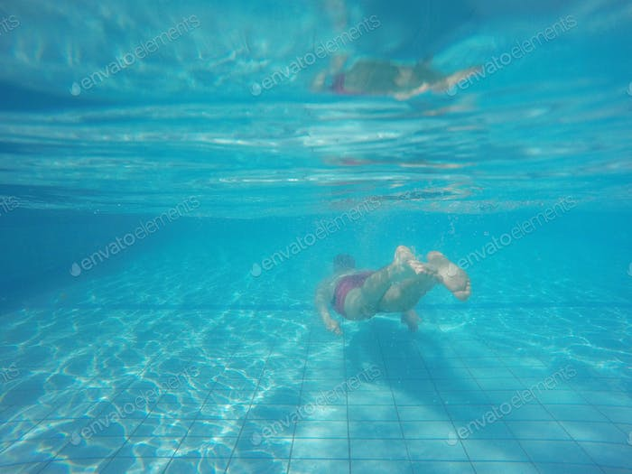 Beard man with glasses diving in a pool