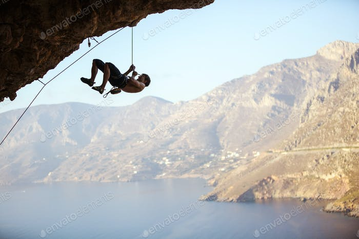 Young man trying to reach cliffliff in order to continue climbing ch