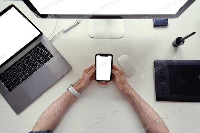 Man hands close up holding a black cell phone with blank white screen