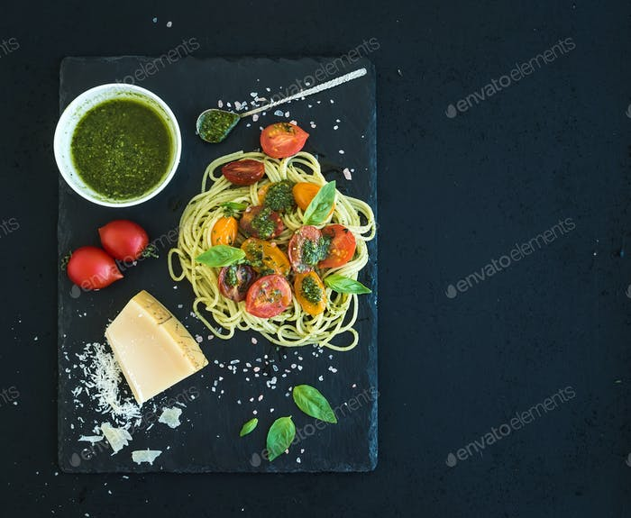 Spaghetti with pesto sauce, roasted cherry-tomatoes, fresh basil and parmesan cheese