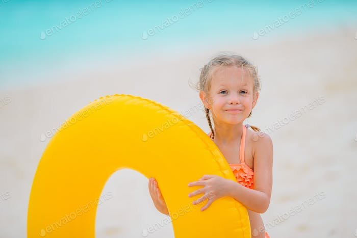 Happy kid with inflatable rubber circle having fun on the beach