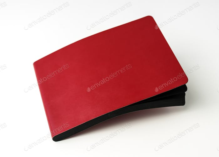 Closeup of red cover notebook on white table