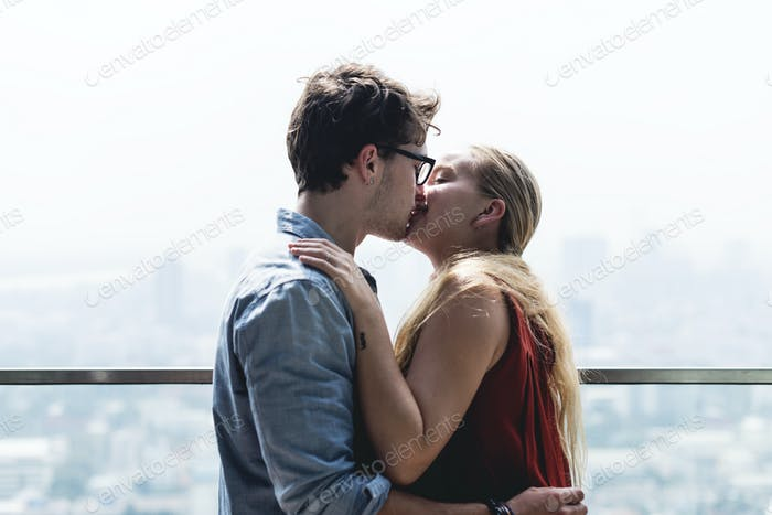 Caucasian couple kissing each other in a cityscape background
