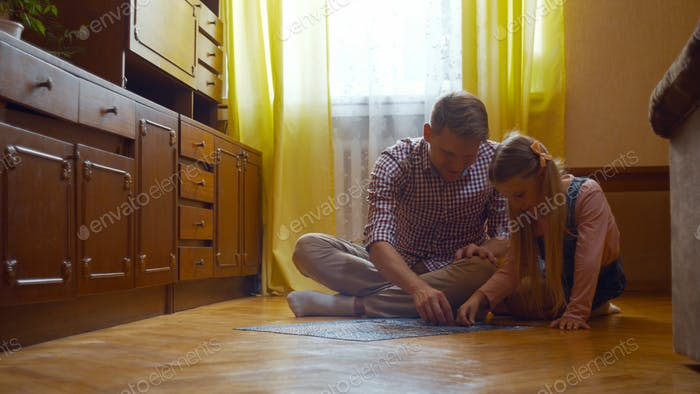 Dad and daughter putting the puzzle