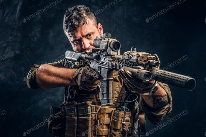 Special forces soldier wearing body armor holding assault rifle and aim at the enemy.