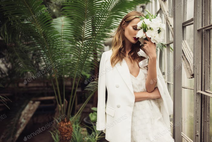 Young attractive woman in white jacket and dress dreamily coveri