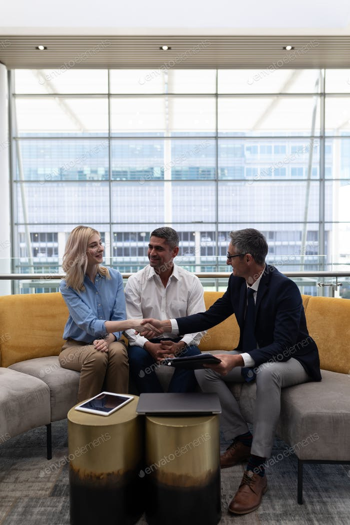 Caucasians business executives shaking hand while sitting on the sofa in modern office.