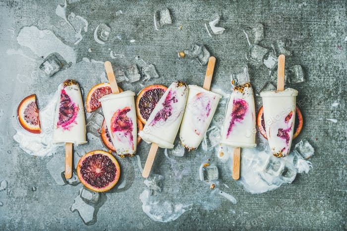Red orange, yogurt, granola popsicles on ice cubes, grey background