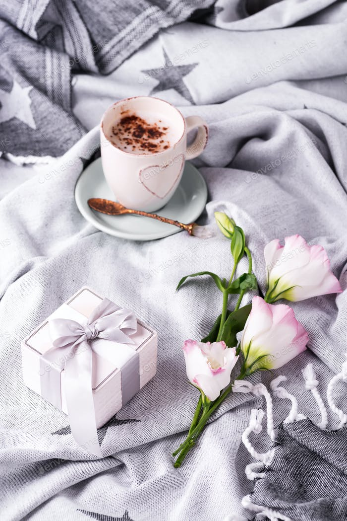Having a cup of coffee with chocolate, flowers eustoma and gift box on blanket in bed. Holiday