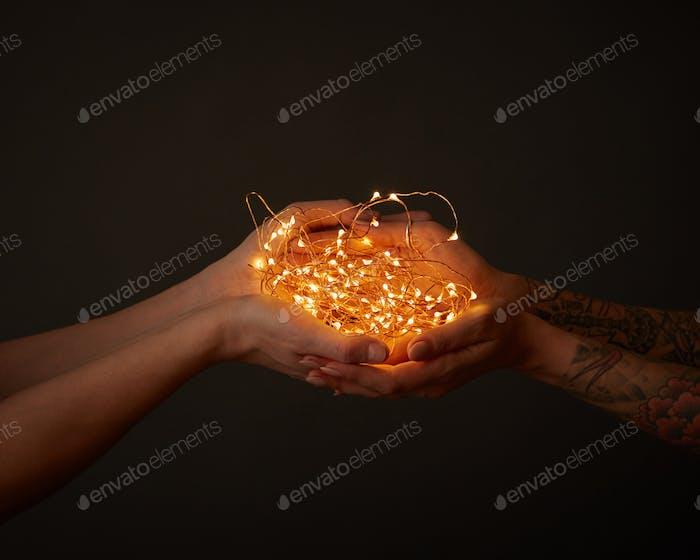 Leuchtende gelbe Girlande, hält weibliche Hand mit Tattoo und männliche Hand um einen dunklen Hintergrund mit