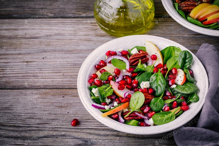 Homemade spinach, apple, pecan, red onion  salad with goat cheese and pomegranate