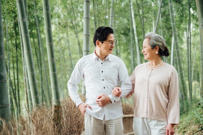 Portrait of senior couple taking a walk in bamboo forest