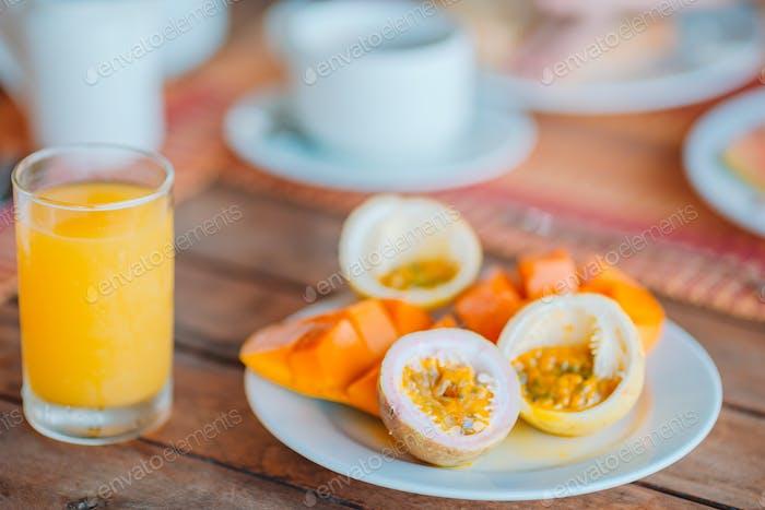 Leckere exotische Früchte - reife Passionsfrucht, Mango beim Frühstück bei Outdoor-Restaraunt