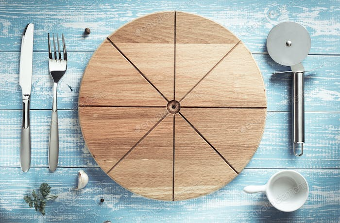pizza cutting board and utensils at wood
