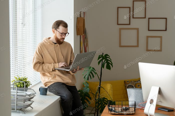 Young bearded freelancer using laptop while networking on windowsill