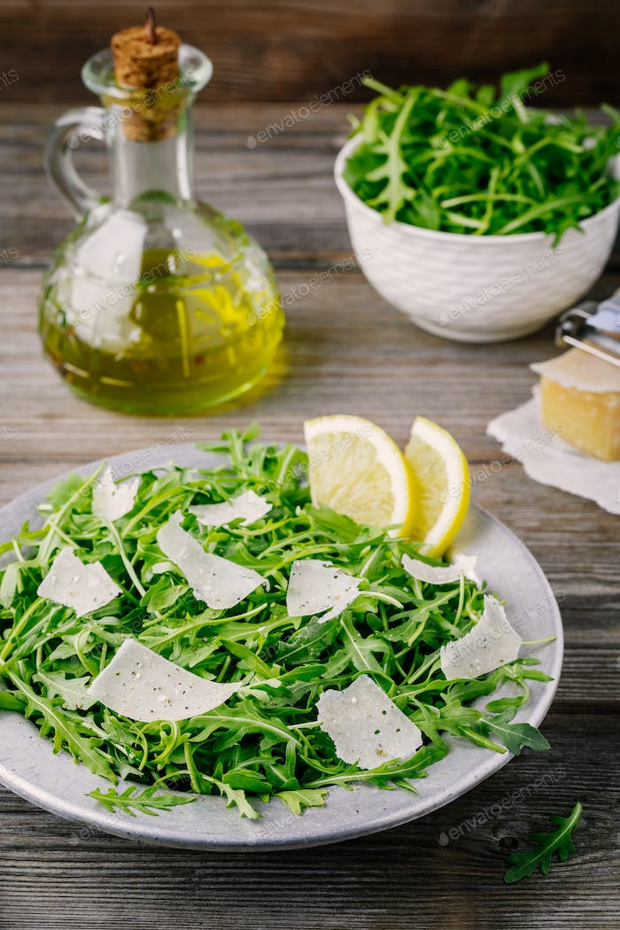Green arugula salad with Parmesan cheese, lemon, olive oil and seasonings