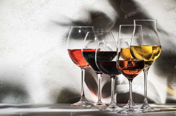 Wines assortment. Red, white, rose wine in wineglasses on gray background. Wine tasting concept