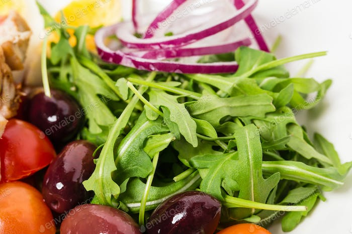 Delicious nicoise salad with arugula and olives.