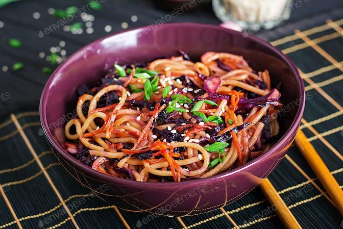 Chinesisches Essen. Vegan rühren Nudeln mit Rotkohl und Karotte in einer Schüssel  braten