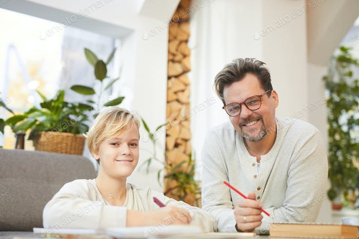 Smiling Father Helping Son with Homework