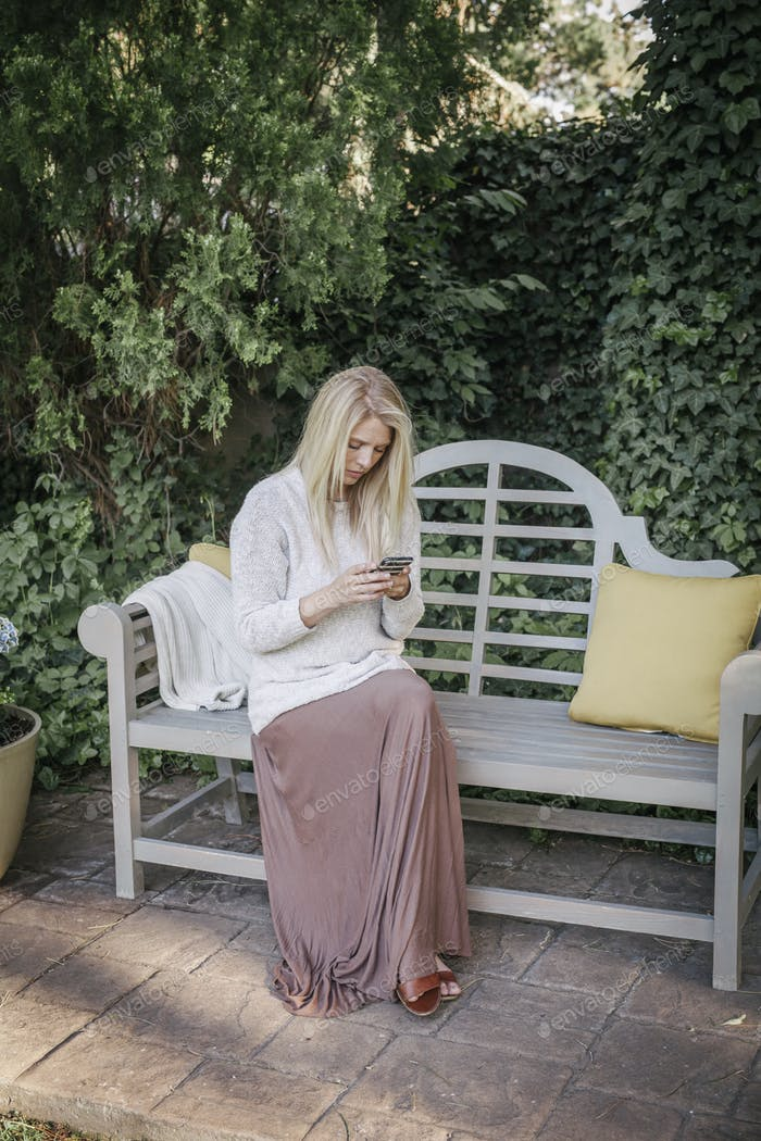 Woman sitting in a garden on a bench, using her mobile phone.