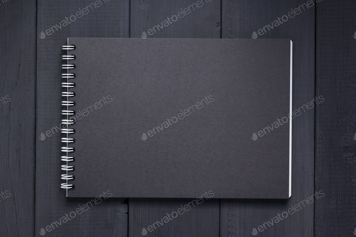 paper notebook at black wooden background