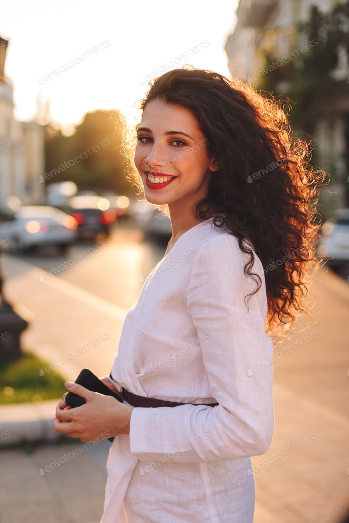 Beautiful smiling lady in white jacket on street joyfully looking in camera with cellphone in hands