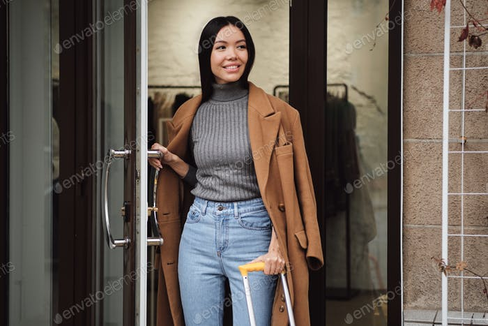 Beautiful casual Asian girl happily looking away leaving fashion store outdoor