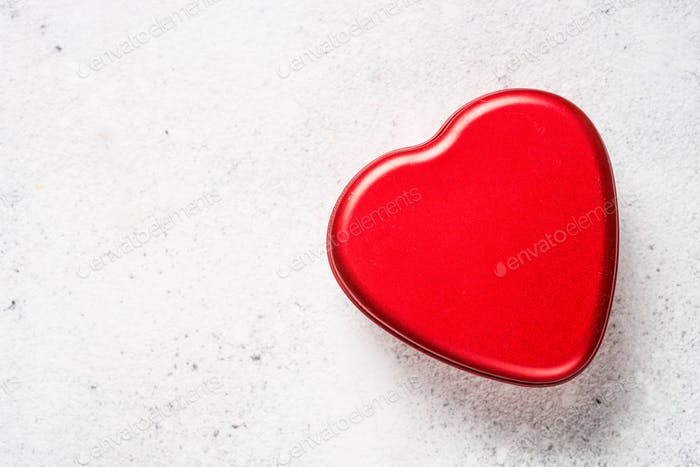 Red heart on white table top view