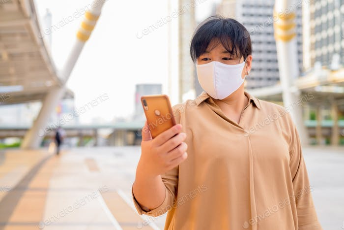 Overweight Asian woman with mask using phone at skywalk bridge