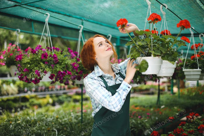 Pretty smiling redhead florist in apron working with flowers. Yo