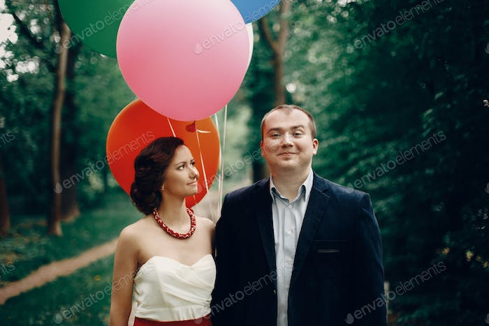 romantic newlyweds posing with balloons outdoors