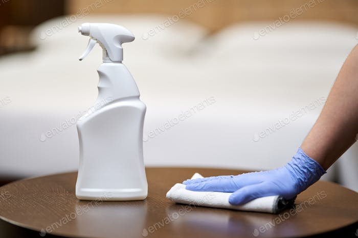 Maid disinfecting furniture with a rag in bedroom