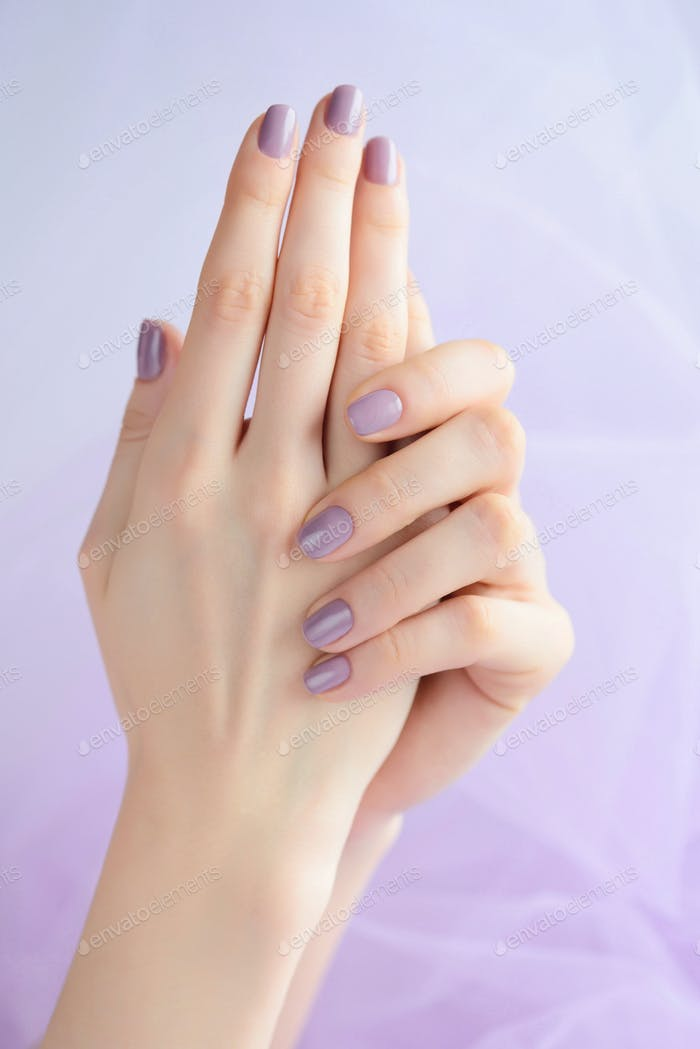 Hands of a young woman with pink manicure on nails