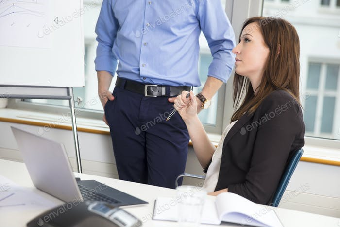 Businesswoman Holding Pen By Colleague In Office