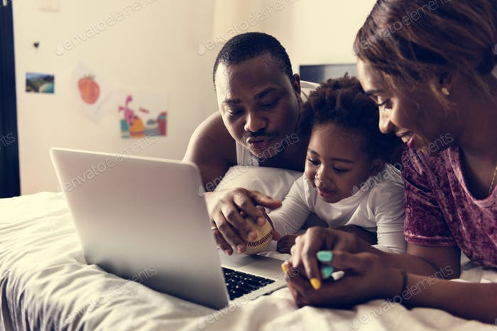 Black family lying on bed using computer laptop together in bedroom