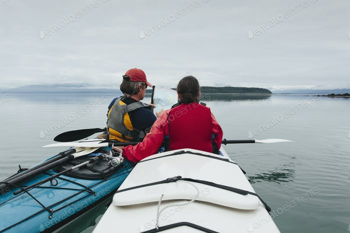 Sea kayakers looking at nautical chart and map,an inlet on the Alaska coastline.