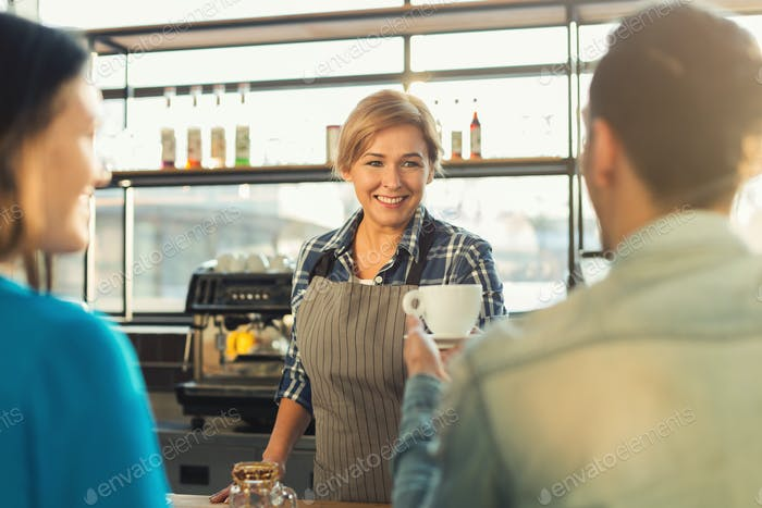Experienced smiling barista making coffee to customers