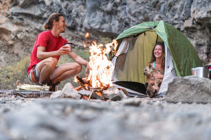 Travel couple camping in rock mountains with their dog