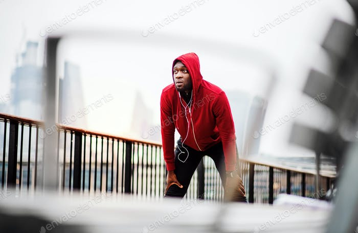 A black man runner with earphones and hood on his head in a city, resting.