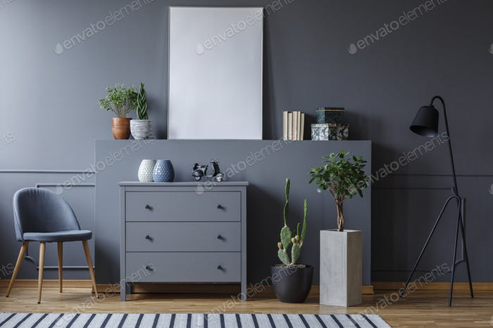 Real photo of a monochromatic living room with a chest of drawer